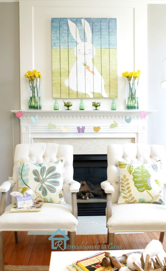 a fun Easter mantel with yellow rose arrangements, a colorful bunny artwork, a bird garland and bottles