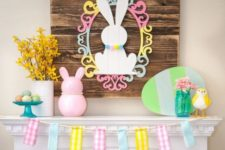 a funny Easter mantel with a bunny sign with a frame, fake bunnies, birds and a cardboard egg