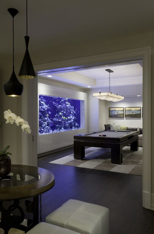 a game room finished with a large aquarium that takes almost the whole wall looks very relaxing and cool