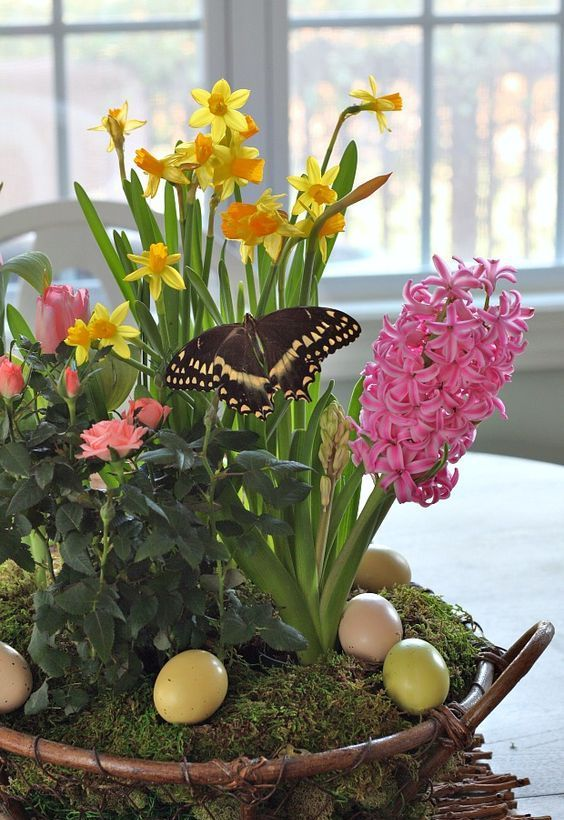 a garden-inspired flower arrangement with colorful spring bulbs in a basket with moss and pastel eggs