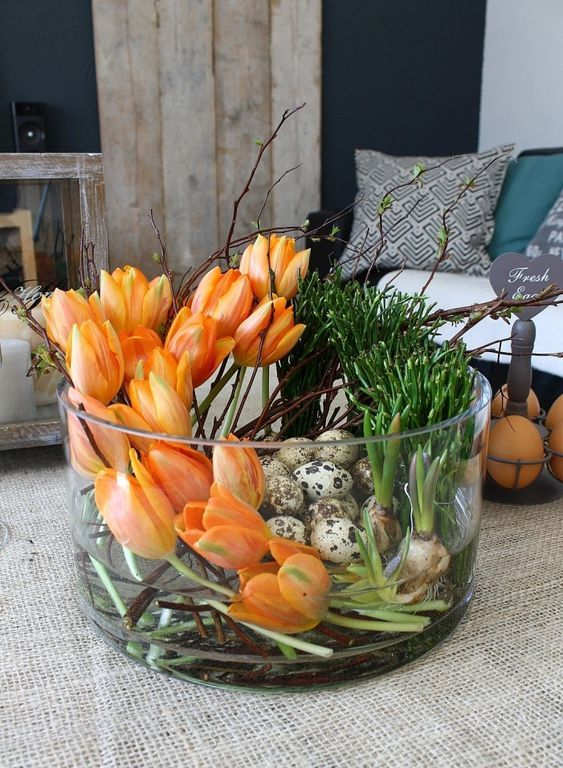 a jar with orange tulips, bulbs and speckled eggs is a bold Easter centerpiece