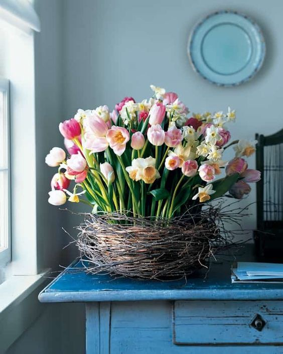 a lush flower arrangement of pink tulips and white daffodils placed in a nest screams Easter