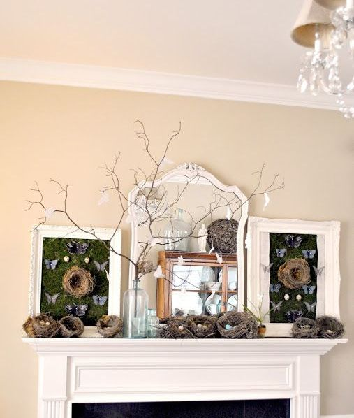 a mantel done with lots of nests with eggs, branches with paper birds and chalkboards with butterflies