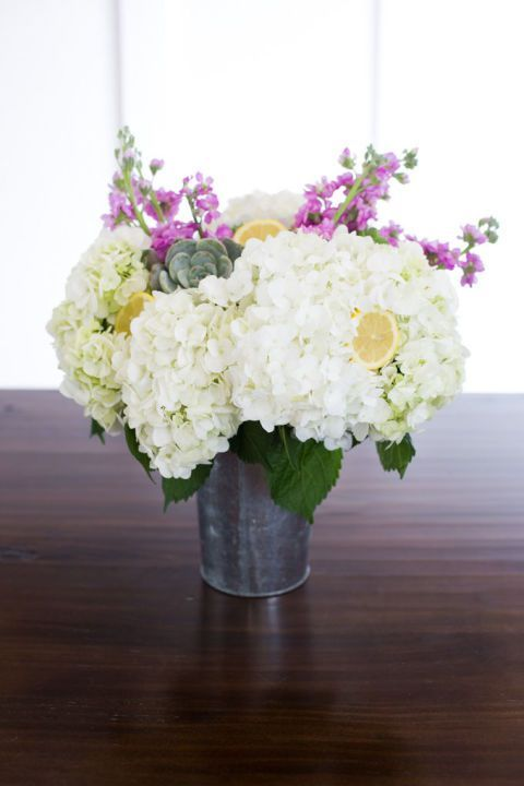 a metal bucket with white hydrangeas, pink blooms, succulents and lemons in it