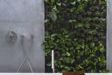 a minimalist bathroom clad with concrete and with a living wall that is a fresh and cool statement for lively decor