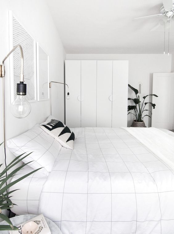 a minimalist meets Nordic bedroom with sleek storage units, a bed, some bulbs and artworks