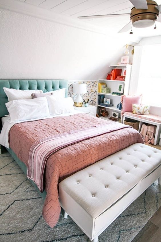 a mint grene upholstered bed, peahcy pink bedding and a floral half wall for a spring feel in the room