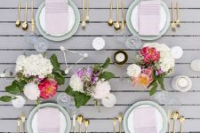 a modenr spring tablescape with bright floral centerpieces, blush napkins and geometric touches