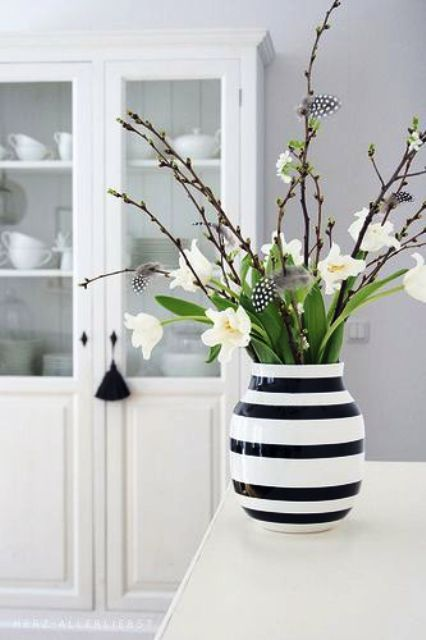 a modern Easter flower arrangement with a black and white striped vase, pussy willow, white blooms and feathers