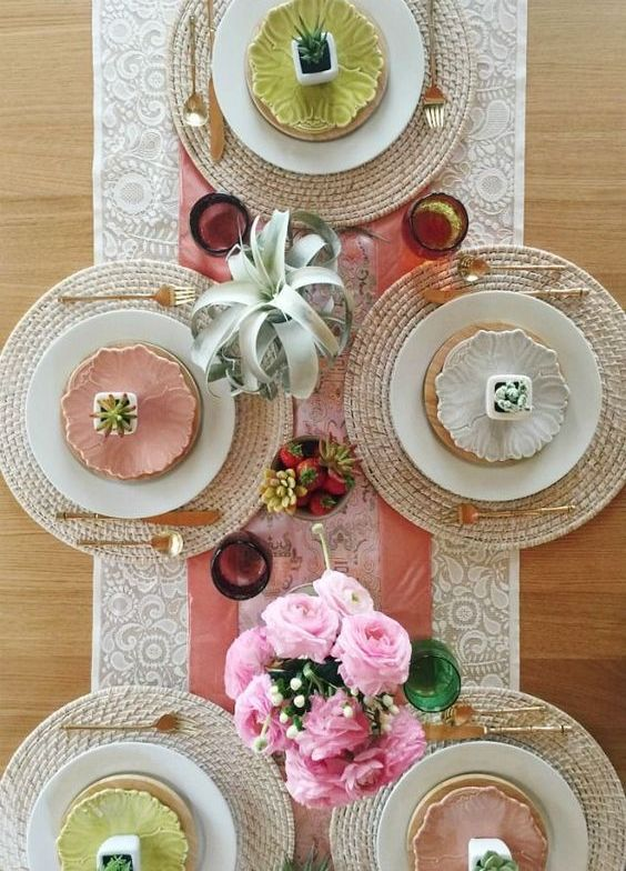 a modern colorful spring tablescape with succulents, pink roses, colorful plates and wicker chargers