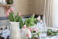 a modern farmhouse spring table setting with blue and white porcelain, pink tulips and a faux nest with eggs