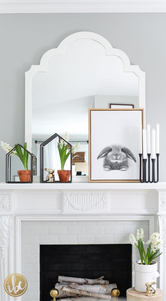 a modern spring mantel with blooming bulbs, a rabbit sign, candles in modern candle holders and a bunny figurine