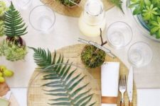 a modern spring table setting with wooden placemats, much fresh greenery and moss, candles and wooden cutlery