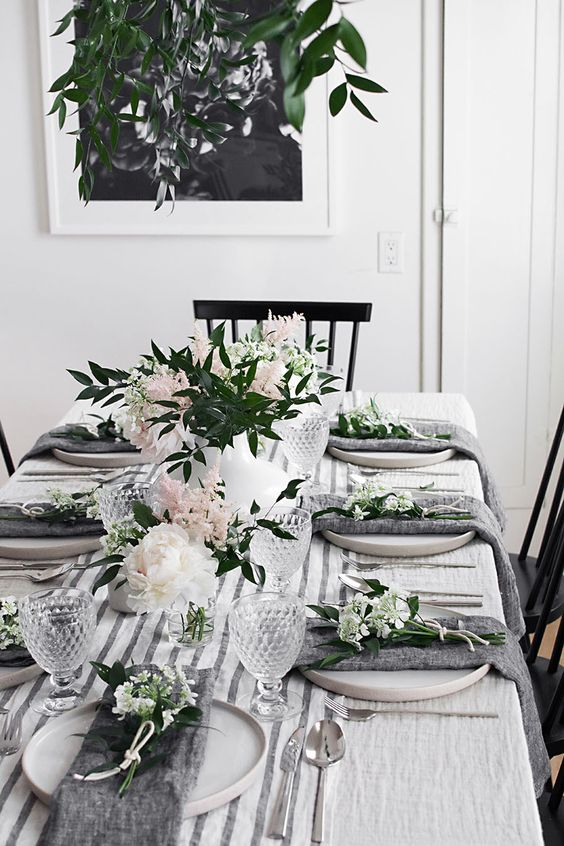 a modern spring tablescape with white and blush blooms and greenery, grey napkins, a striped runner and cool glasses