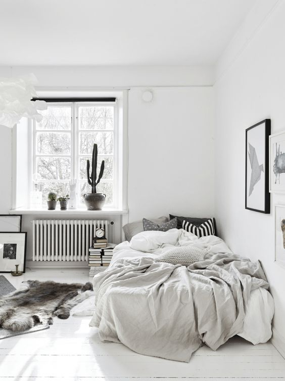 a monochromatic Nordic bedroom with some potted cacti, a bed in the corner, books and artworks