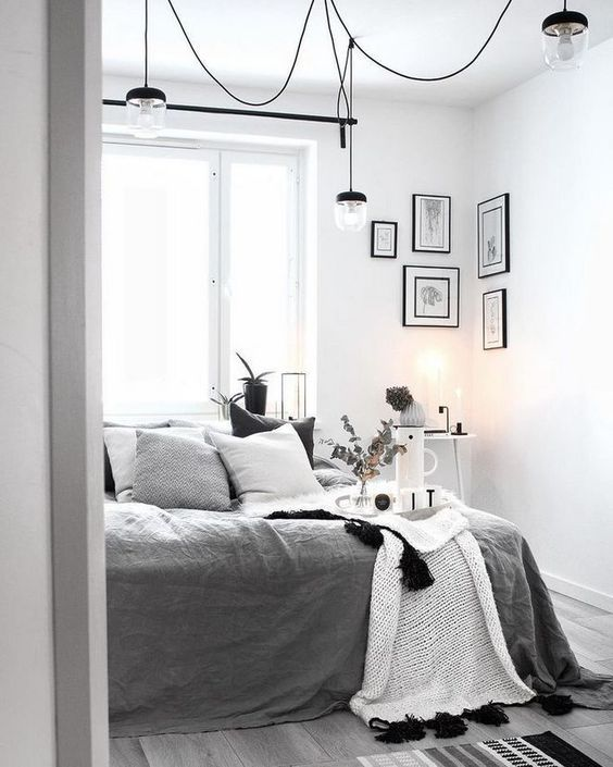 a monochromatic Scandi bedroom with a bed with grey and white bedding, some lamps, lights and a gallery wall