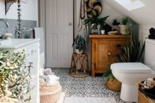 a monochromatic attic bathroom with potted greenery and succulents that add a fresh and cool feel to the space