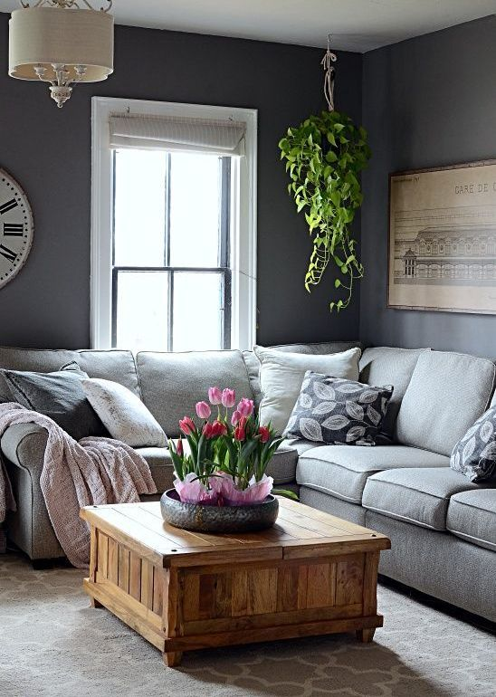 a monochromatic living room with potted plant and some tulips that refresh the space and make it spring-like