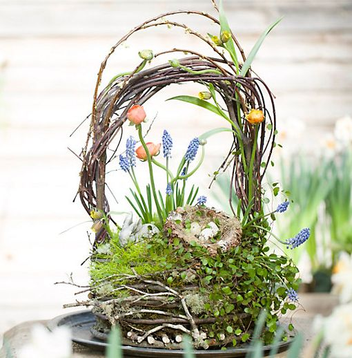 a nest Easter arrangement with a handle, grape hyacinths, other bulbs, moss and greenery and some fake eggs