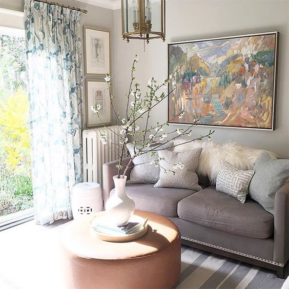 a neutral and pastel living room with grey walls and a sofa, blue touches, floral curtains and a striped rug plus blooming branches