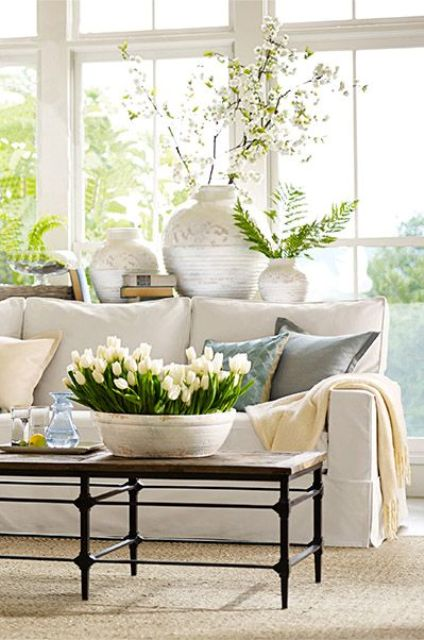 a neutral and pastel living room with potted greenery and blooms, with printed vases and a glazed wall is fresh and spring-like