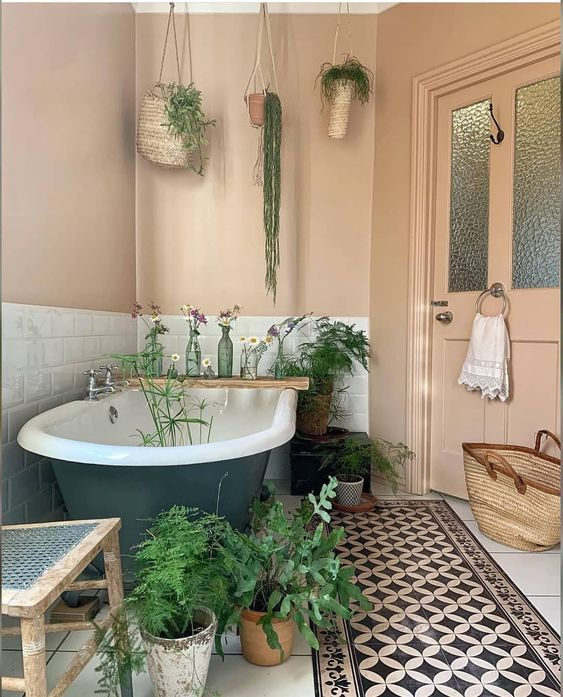 a neutral bathroom with greenery on the floor and hanging from the ceiling is a warm and cool space