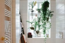 a neutral bathroom with potted plants and kokedama on the window that refresh this space