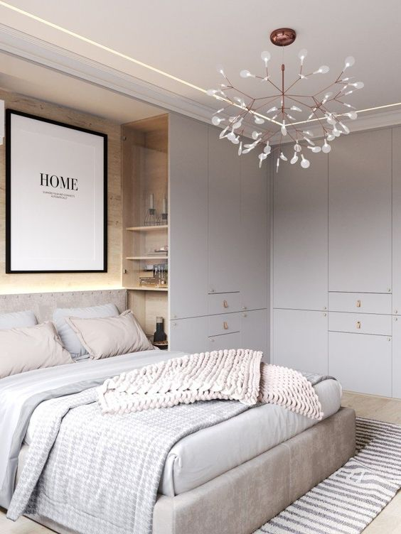 a neutral bedroom with light grey, off-white and touches of blush, built-in storage units and shelves
