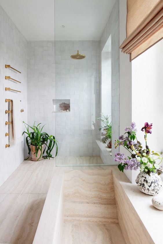 a neutral contemporary bathroom with blooms and greenery in pots and touches of gold for a chic and lively look