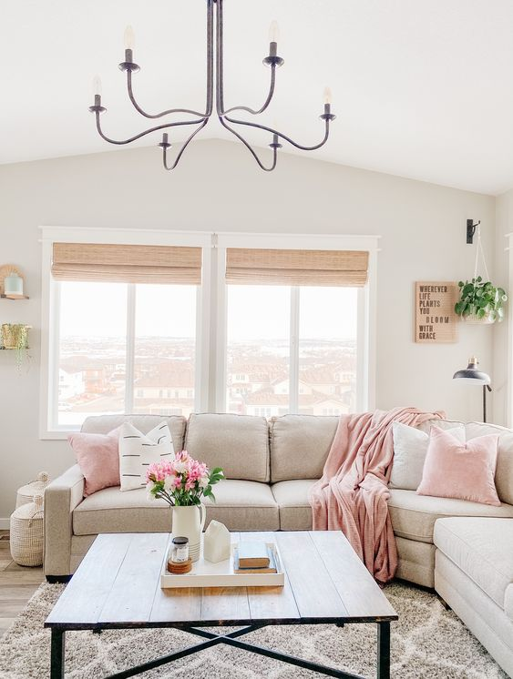 a neutral farhouse livng room with light pink linens, potted greenery and blooms and a printed rug is welcoming