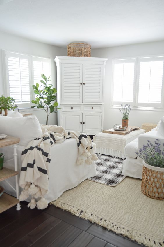 a neutral farmhouse living room with neutral furniture, printed textiles, potted greenery and some lavender feels like spring