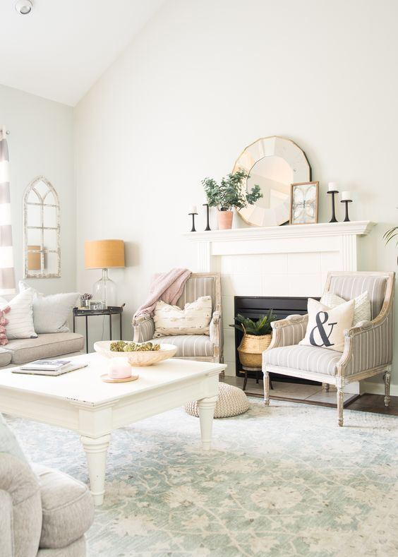 a neutral farmhouse living room with printed chairs and a printed rug, potted greenery, pink linens and mirrors