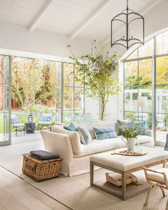 a neutral light-filled farmhouse living room with greenery, blooms and a tree in a pot is a chic space to be