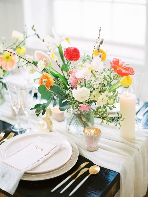 a neutral runner, a colorful floral centerpiece, candles, gilded cutlery and pastel plates for a vibrant look