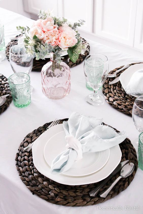 a neutral spring tablescape with pastel glasses and blooms is added drama with dark wicker chargers