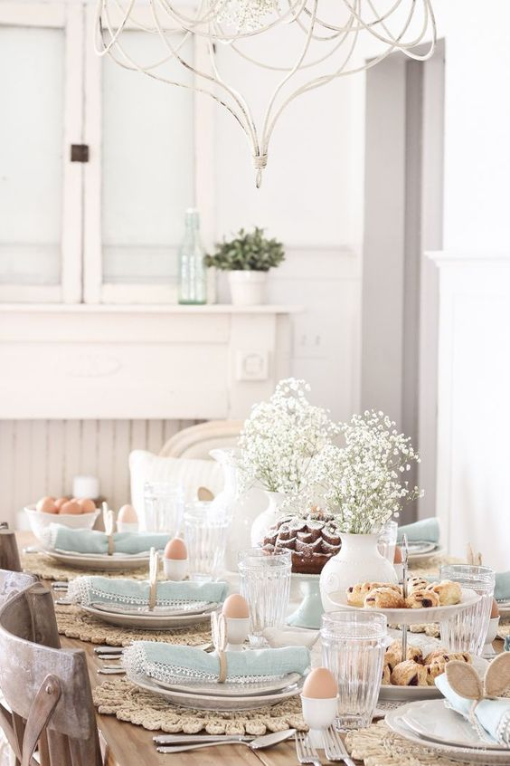 a pastel vintage-inspired tablescape with a baby's breath centerpiece, wicker chargers, blue napkins and bunny ear napkin rings