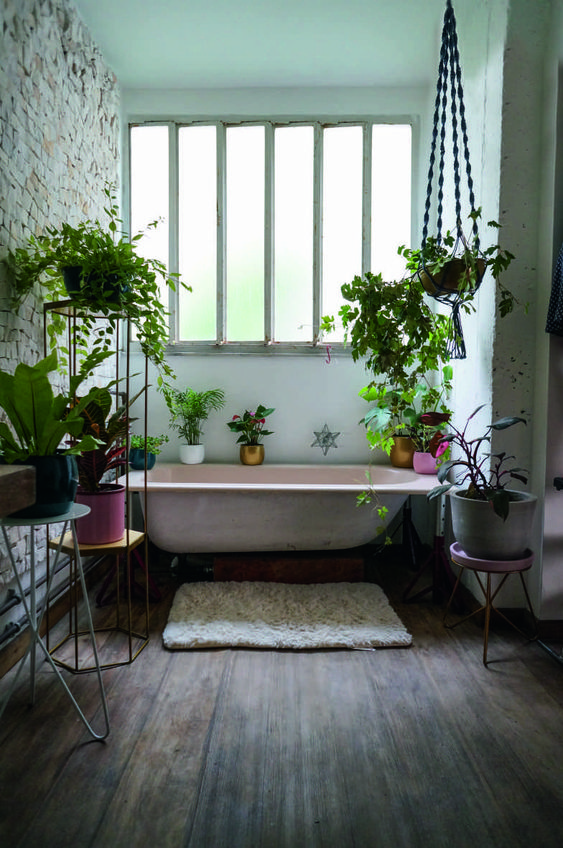 a pretty moody bathroom with a pink tub, colorful planters with greenery all around and a brick wall for interest