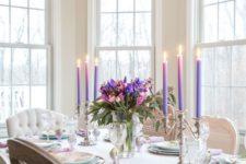 a refined colorful spring tablescape with a bright floral centerpiece, purple candles, printed plates and chargers