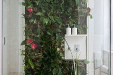 a shower space with a statement living wall that adds a vivacious and fresh feel to the space