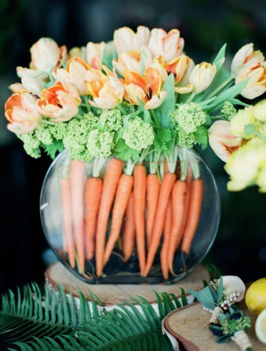 a simple Easter arrangement of carrots, greeneyr and orange tulips in a large rounded vase