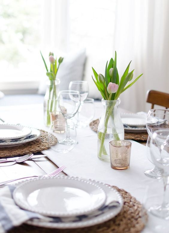 a simple and modern wedidng tablescape with a white table runner, tulip centerpieces, wicker chargers and white porcelain