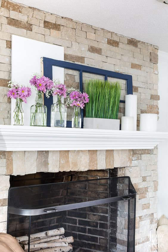 a simple spring mantel with grass in a pot, pillar candles and some pink floral arrangements in clear vases