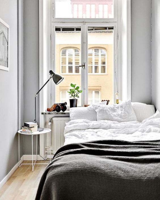 a small Nordic bedroom with a bed, a nighstand with a lamp, potted greenery and grey walls
