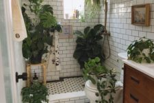 a small and neutral bathroom with a wooden vanity, lots of greenery in pots and some suspended plants