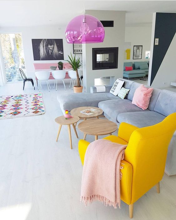 a spring living room zone with a bold yellow chair, pink linens, a hot pink sheer pendant lamp