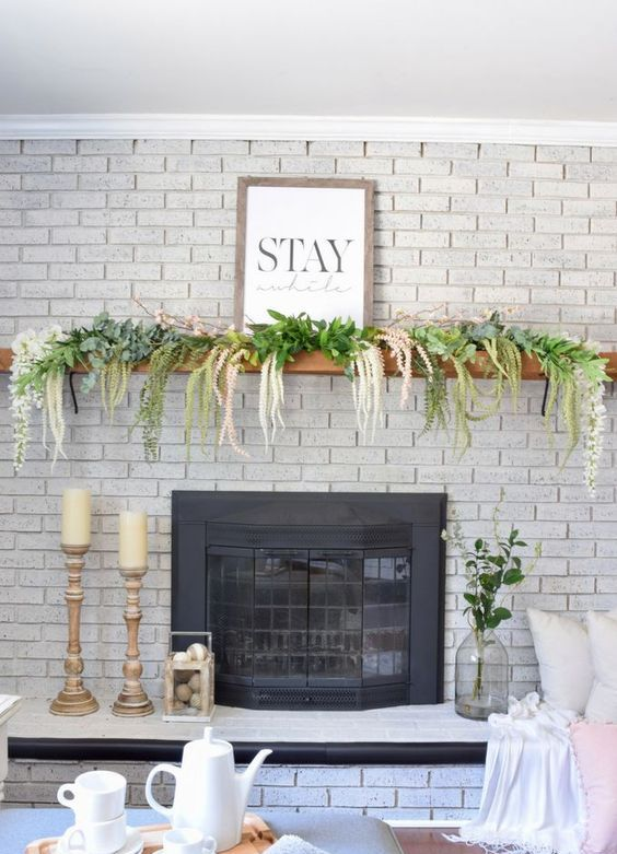 a spring mantel with cascading florals and greenery plus a sign, fake eggs in a lantern by the fireplace