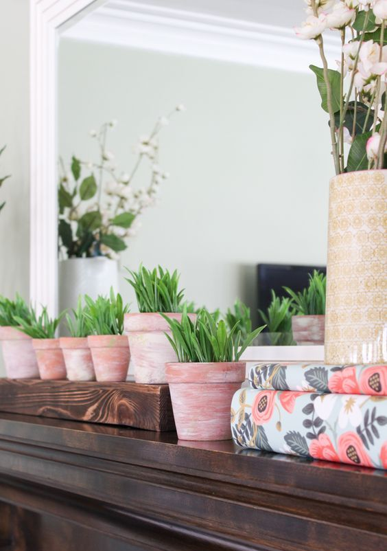 a spring mantel with potted greenery, blooming branches and floral print paper