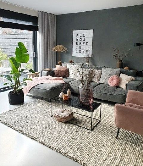 a spring-ready living room with a grey sofa, a pink chair, pillows and blankets, some branches in vases and a statement plant