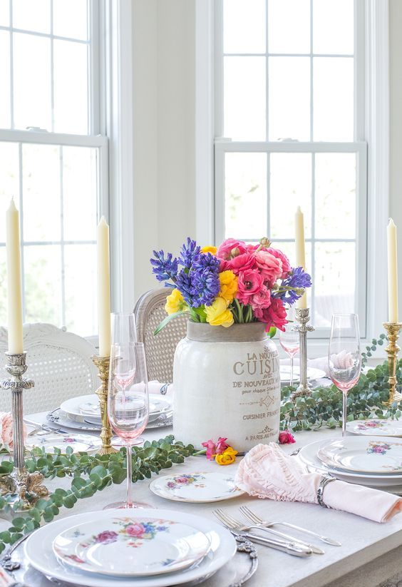 a spring tablescape with bright porcelain, a colorful floral centerpiece, a eucalyptus runner, candles and pink napkins