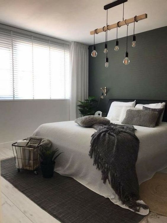 a stylish Scandi bedroom with a black statement wall, a black bed, a hanging piece with bulbs and a rug